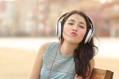 Jugendlichmädchen mit Kopfhörern küssend an der Kamera Stockfoto
