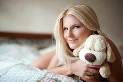 Jugendlichmädchen mit Spielzeug auf ihrem Bett Stockbilder