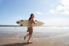 Jugendlichmädchen mit Surfbrett Stockfotos