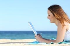 Jugendlichmädchengrasensocial media in einer Tablette auf dem Strand Stockfotografie
