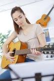 Jugendlichm?dchen-Gitarrenspiel stockfoto