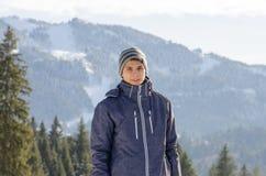 Jugendlichmann, der in der Winterjacke an den Bergen mit Skischweinefutter lächelt Stockfotografie