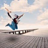 Jugendlichmädchen, das E-Gitarre auf einem Kai spielt Lizenzfreies Stockbild