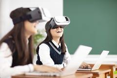 Jugendlichstudent mit Kopfhörer der virtuellen Realität im Klassenzimmer stockfotografie