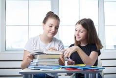 Jugendlichteenagerstudenten sitzen am Tisch mit Buchst. stockfoto