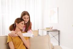 Jugendlichtochter, die ihre Mutter umarmt stockfoto
