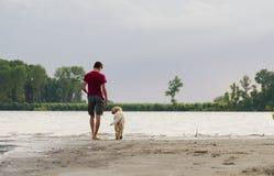 Jugendlichweg mit Hund auf dem Strand des Flusses Stockfoto