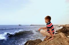 Jugendlookeing weit entfernt auf Küste des Meeres Stockfoto