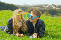 Jugendpaare in den sehr großen lustigen Gläsern Lizenzfreies Stockfoto