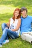 Jugendpaare, die auf dem Gras umfasst Sommer sitzen Lizenzfreie Stockfotografie
