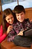 Jugendpaare, die auf Sofa mit Laptop sich entspannen Stockbild