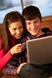 Jugendpaare, die auf Sofa mit Laptop sich entspannen Lizenzfreie Stockbilder