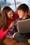 Jugendpaare, die auf Sofa mit Laptop sich entspannen Lizenzfreies Stockbild