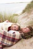 Jugendpaare, die in den Sanddünen liegen Stockbild