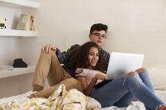Jugendpaare, die heraus in aufpassendem Laptop des Schlafzimmers hängen Stockbilder