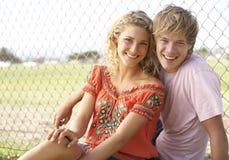 Jugendpaare, die im Spielplatz sitzen Lizenzfreie Stockfotografie