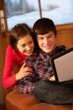 Jugendpaare, die mit Tablette-Computer sich entspannen Stockfotografie