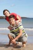 Jugendpaare, die Spaß auf Strand haben Stockbild