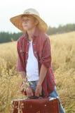 Jugendreisender auf dem Bauernhofhafergebiet, das altmodischen Koffer hält und zum Horizont schaut Lizenzfreie Stockfotografie