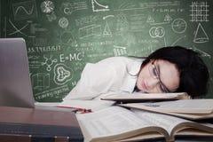 Jugendschulmädchen, das auf Schreibtisch schläft Stockfotos