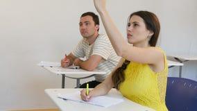 Jugendstudenten, die in Klassenzimmer-antwortender Frage studieren Stockbild