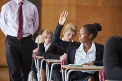Jugendstudenten-Sitting Examination Asking-Lehrer Question lizenzfreie stockfotografie