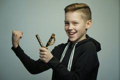Jugendunartiger junge mit Katapult und stilvollem Haarschnitt, Atelieraufnahme stockbild