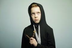 Jugendunartiger junge mit Katapult und stilvollem Haarschnitt, Atelieraufnahme lizenzfreie stockfotos