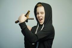 Jugendunartiger junge mit Katapult und stilvollem Haarschnitt, Atelieraufnahme stockfotografie