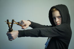 Jugendunartiger junge mit Katapult und stilvollem Haarschnitt, Atelieraufnahme stockfoto