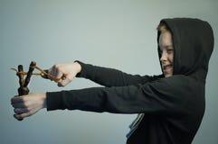 Jugendunartiger junge mit Katapult und stilvollem Haarschnitt, Atelieraufnahme Lizenzfreie Stockbilder