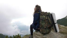Jugendwandererfrau mit dem Rucksack, der allein auf der Gebirgshohen Klippe die erstaunliche Landschaft friedlich bewundernd sitz stock footage