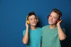 Jugendzwillingsbrüder mit Kopfhörern stockfotos