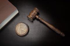 Juges Gavel et livre de loi sur le fond en bois noir Image stock