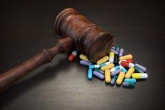 Juges Gavel et médicament sur le fond grunge en bois noir Images stock