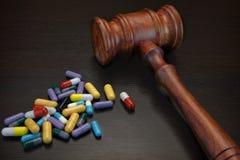 Juges Gavel et médicament sur le fond grunge en bois noir Image libre de droits