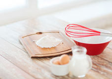 Jugful of milk, eggs in a bowl and flour Royalty Free Stock Photography