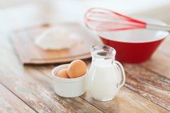 Jugful mleko, jajka w pucharze i mąka, obrazy stock