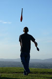 Juggler. A man juggling on a hill top at dusk stock photography