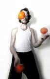 Juggler. Young male juggler, throwing oranges Stock Photo