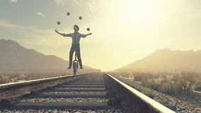 Juggler is balancing on railroad. With a bike and balls. This is a 3d render illustration royalty free illustration