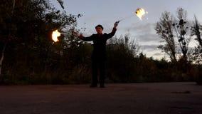 Juggler de Stokken van Turns Two Burning rond zich het kijkt Verblindend in slo-Mo stock video