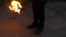 A Juggler Man Swings Two Lit Balls of Fire Outdoors in Autumn in Slow Motion. An Exciting View of a Juggler Man Who Waves Two Lit Balls of Fire on Metal Cords stock video footage