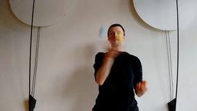 Juggler with three color balls before white wall with decoration on sides stock video