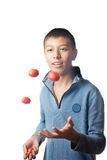 Juggler and tomato. Studio photo of the young boy juggling with tomato stock image