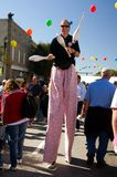 Juggler walks on stilts. Juggler with three pins walks, using stilts, through the festival crowd. This man is hired by the festival authority. Stop-action photo Stock Photos