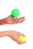 Juggling 2 balls. Side shot of hands juggling 3 balls against a white backdrop stock photography