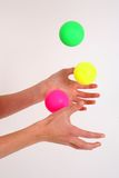 Juggling 3 balls. Side shot of hands juggling 3 balls against a white backdrop Stock Photo