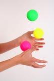Juggling 3 balls. Side shot of hands juggling 3 balls against a white backdrop stock photo