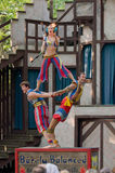 Juggling Acrobats. A trio of acrobats performs a stunt involving juggling flaming torches Stock Photo